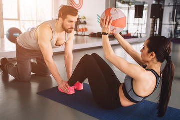 A picture of girl doing some abs exercise with the ball while her sport partner is holding her legs down on the floor. He helps her to do exercise in proper way.