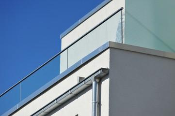 Attika-Profilblech als Mauerschutz und Kasten-Stahl-Dachrinnen am Dachgeschoss eines modernen Mehrfamilienhauses