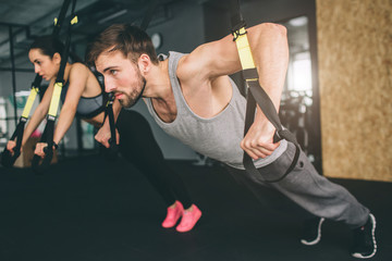 Young man and woman are doing TRX chest press exercise. He is doing push up while she is doing oush down. Close up. Cut view.