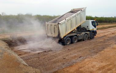 View of dump truck dumping gravel