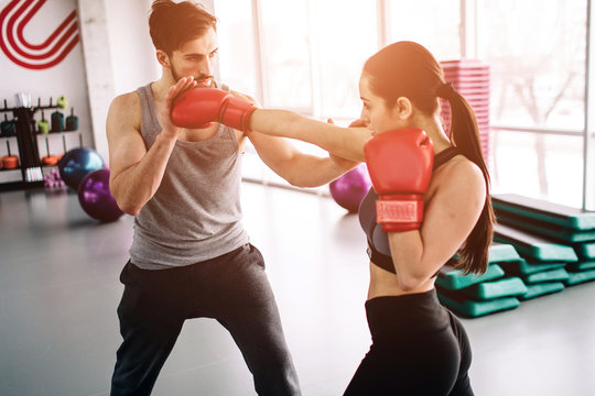 Hansome and well-built partners are boxing together. She attackes hi, while he is trying to defennce himself and also trying to attack. They are concentrated and concious