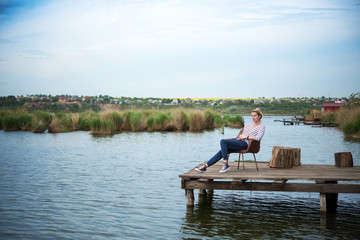 Photo of young woman sitting in old chair on the pier on the lake. Happiness, inspiration and relax concept.
