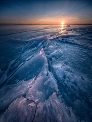 Seascape at winter with ice details and golden sunset