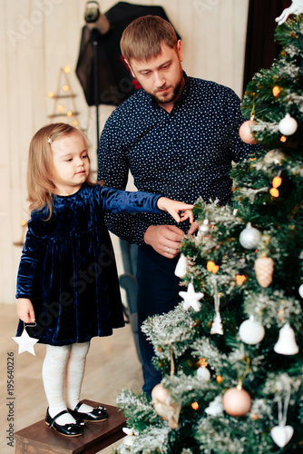 young dad and little daughter in the new year decor with gifts