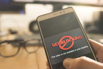 Hands using a smartphone and being unable to navigate online. Geoblocking concept.