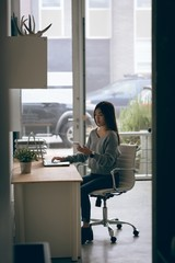 Young businesswoman using mobile phone while working on laptop in office