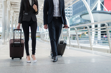 businessman and businesswoman walk together with mobile tablet and luggage on the public street, business travel