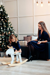 young mother and little daughter in the New Year decor with gifts