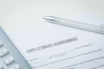Agreement of Employment with pen and laptop lying on a desk in a close up overhead view in a concept of employment and human resources