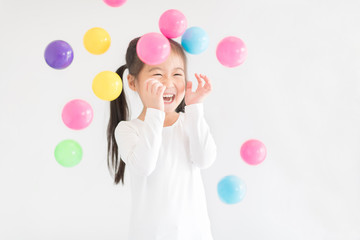 Little girl happy to play with colourful balls. Educational toys for preschool and kindergarten child. Little girl on Daycare Education concept.