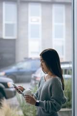 Executive using mobile phone while having coffee