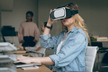 Executive working on laptop while using virtual reality headset