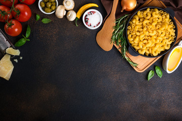 Pasta and ingredients for cooking on dark background, top view. Italian food concept. Pasta, tomatoes, basil, vegetables and spices. Copy space