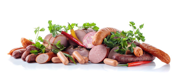 Fototapete - Different sausages and smoked meats isolated on white .