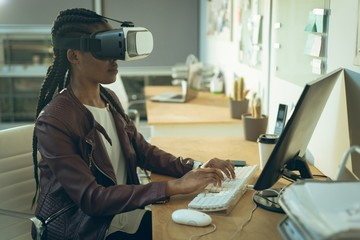 Executive working on computer while using virtual reality