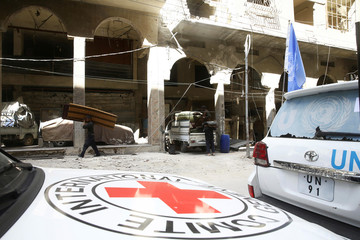 People carry their belonging next to International Red Cross (ICRC) and U.N aid convoys in the besieged town of Douma