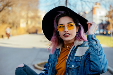 Gorgeous urban girl with hat and yellow sunglasses sitting at city park.