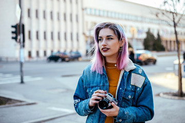 Image of beautiful female student or photographer with pink hair at city street.
