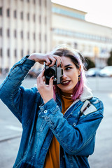 Young woman photographer takes images with camera at city street.