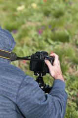 Young male photographer taking photo by DSLR camera. Nature and landscape photography