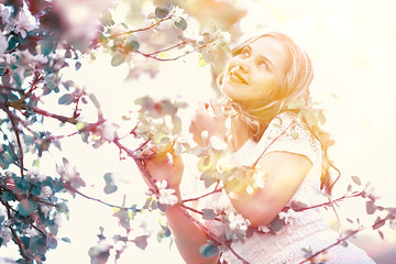 girl sniffing flowers / fresh spring flowers of apple, portrait of a girl in a beautiful spring garden