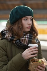 Woman in winter clothing having a wrap and coffee