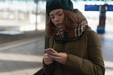 Woman in winter clothing using mobile phone