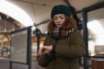 Woman in winter clothing looking at smartwatch