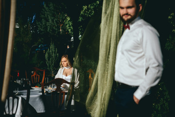 bride and groom sitting in a cozy cafe on the summer terrace. Newlyweds wedding day. Urban space resaurant.