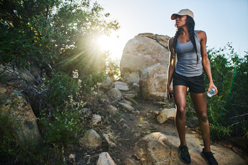 fit female hiker walking down rocky path while holding smartphone and waterbottle Wall mural
