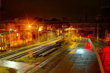 Industriebahnhof Rangierbahnhof bei Nacht mit vielen Lichtern und Waggons auf einem Abstellgleis in einer Industrieanlage mit violetter Optik