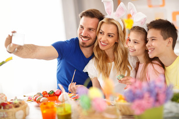 Family making selfie while coloring eggs