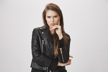 Offended gloomy girlfriend waiting for apology. indoor shot of good-looking urban woman in trendy leather jacket, frowning, holding hand on face, staring with contempt at camera over gray background