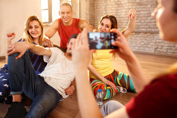 Girl making photo of his friends from dancing room