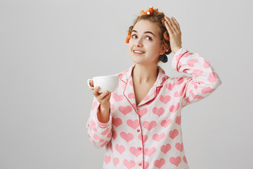 Dreamy cute girlfriend wearing pajamas with heart print and hair curlers, touching them while smiling and drinking cup of coffee, admiring how charming she will look, standing over gray background.