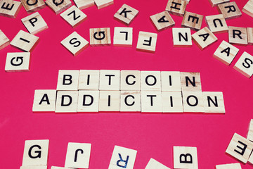 Wooden blocks on a red background spelling words Bitcoin addiction