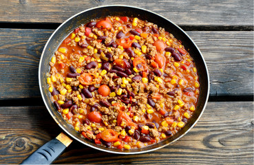 Chili con carne in pan on wooden floor