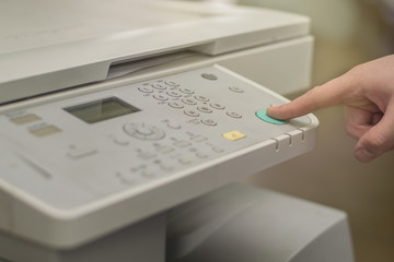 Copier Start, Finger pressing the start button on a multifunction printer or copier
