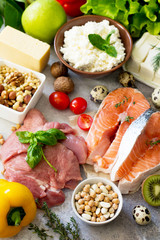 Assortment of a healthy protein source, superfoods on a gray stone background. Meat turkey, salmon, quail eggs, dairy products feta cheese and cottage cheese, beans, spinach, chickpeas, fruit.