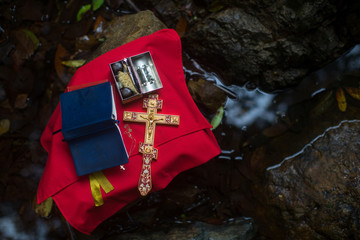 Holy Bible and the Orthodox Cross during the sacrament of baptism outdoors.