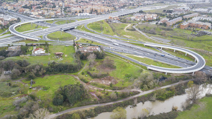Aerial view of a series of ramps of the Rome motorway junction. Many cars, motorcycles and trucks drive on the road. Around there are grass, meadows and green trees.