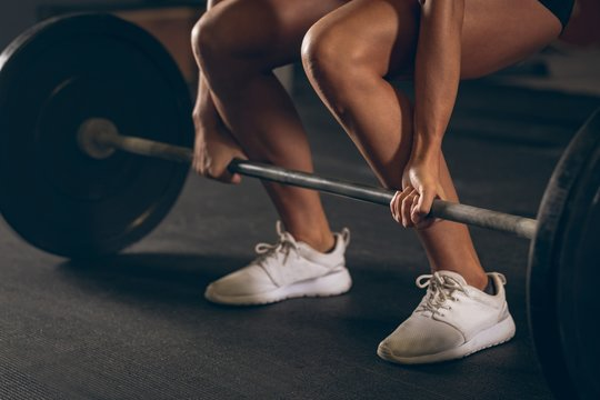 Fit woman lifting the barbell in the gym