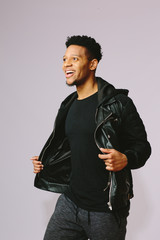 Cool city guy  in casual clothes smiling and holding his jacket, isolated on grey background