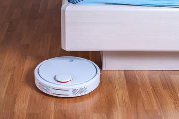 white Robot vacuum cleaner runs under bed in bedroom