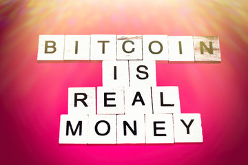 Wooden blocks on a red background spelling words Bitcoin is real money