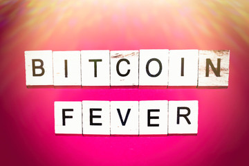 Wooden blocks on a red background spelling words Bitcoin fever