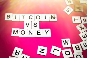 Wooden blocks on a red background spelling words Bitcoin vs money