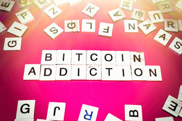 Wooden blocks on a red background spelling words Bitcoin addicion