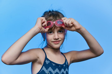 girl with glasses for swimming on blue background