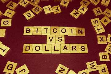 Wooden blocks on a brown background spelling words Bitcoin vs Dollars
